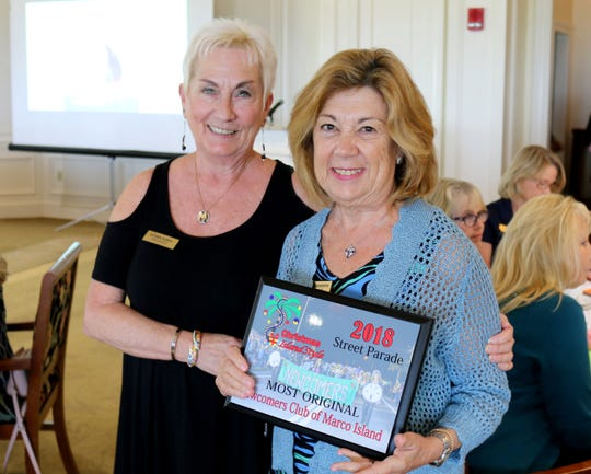 President Donna Dubey presents Laura Geberth with the Newcomers' Christmas Island Style Street Parade Most Original Award.