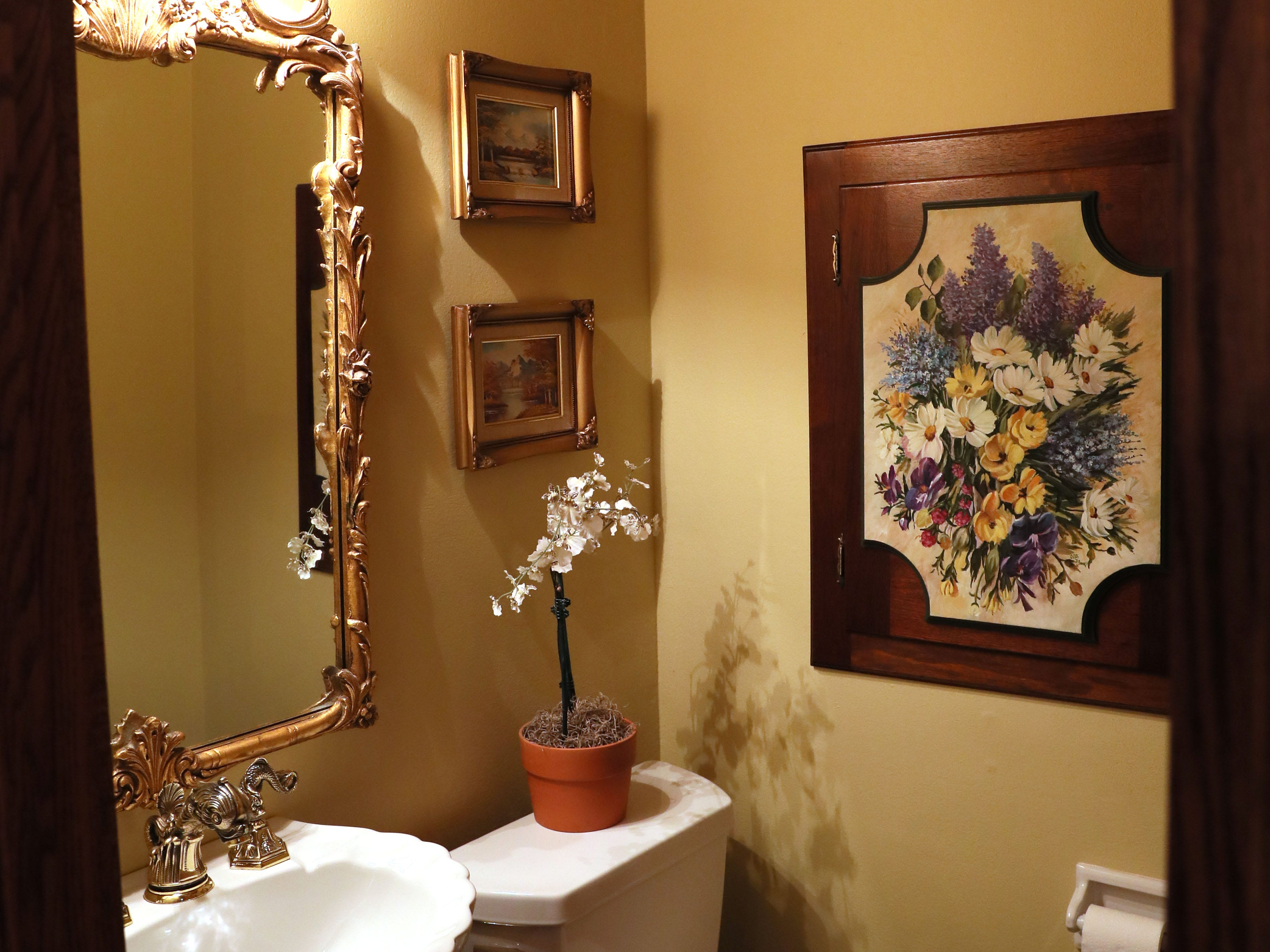 The powder room is painted in a soothing yellow.