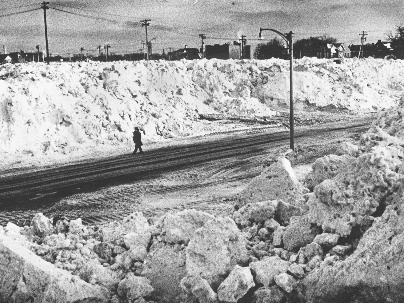 A solitary figure walks down North 26th Street between North Avenue and Meinecke Street, which has been turned into a mountain range made up of snow plowed from city streets on Jan. 30, 1979. The land was vacant because it had been cleared for the planned Park West Freeway, which was never built. This photo was published in the Jan. 31, 1979, Milwaukee Journal.
