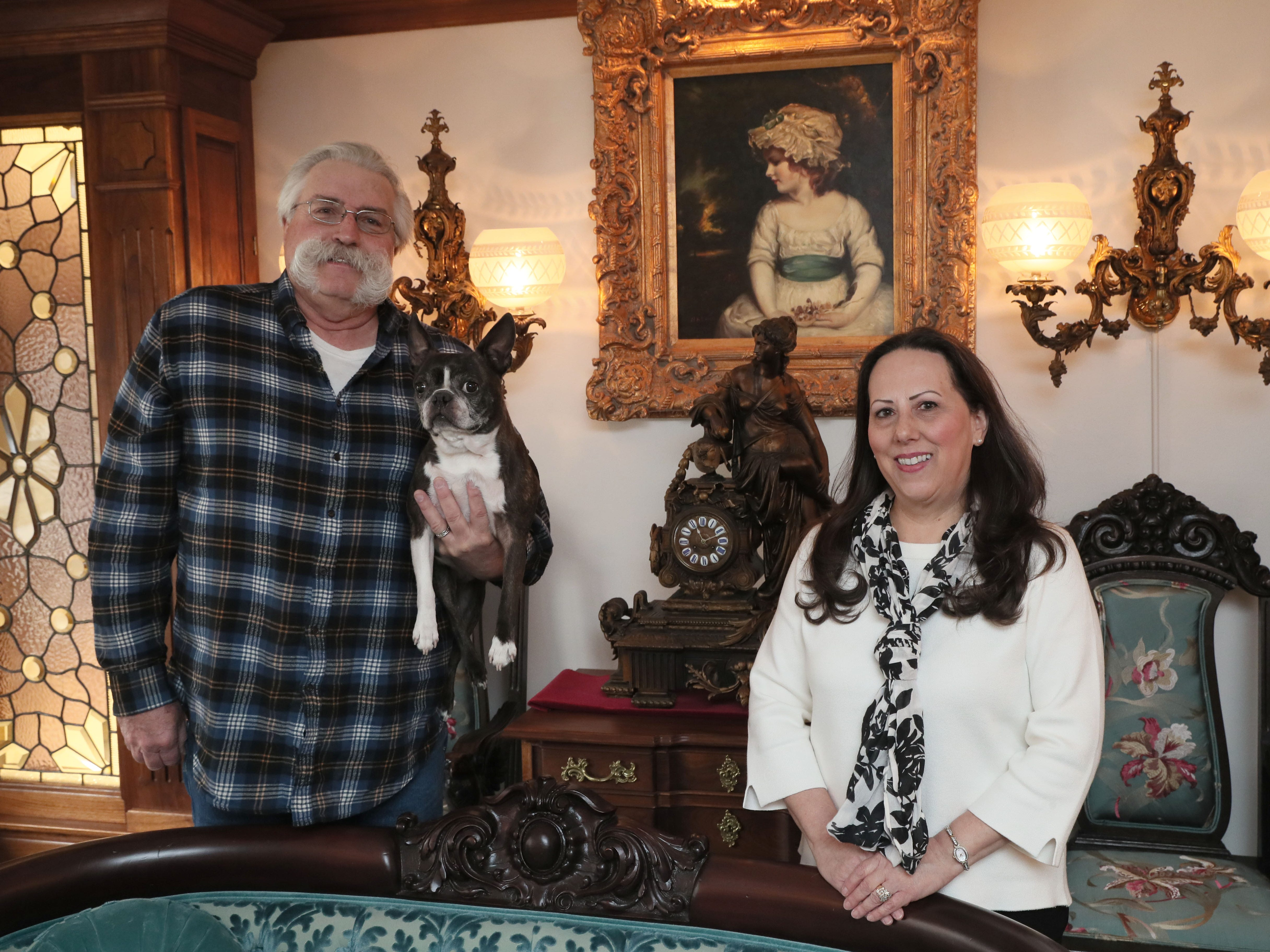 Jim Wissing, holding the family dog Ruby, and his wife, Jennifer, decorated their ranch home with antiques that give it the feel of a Victorian mansion.