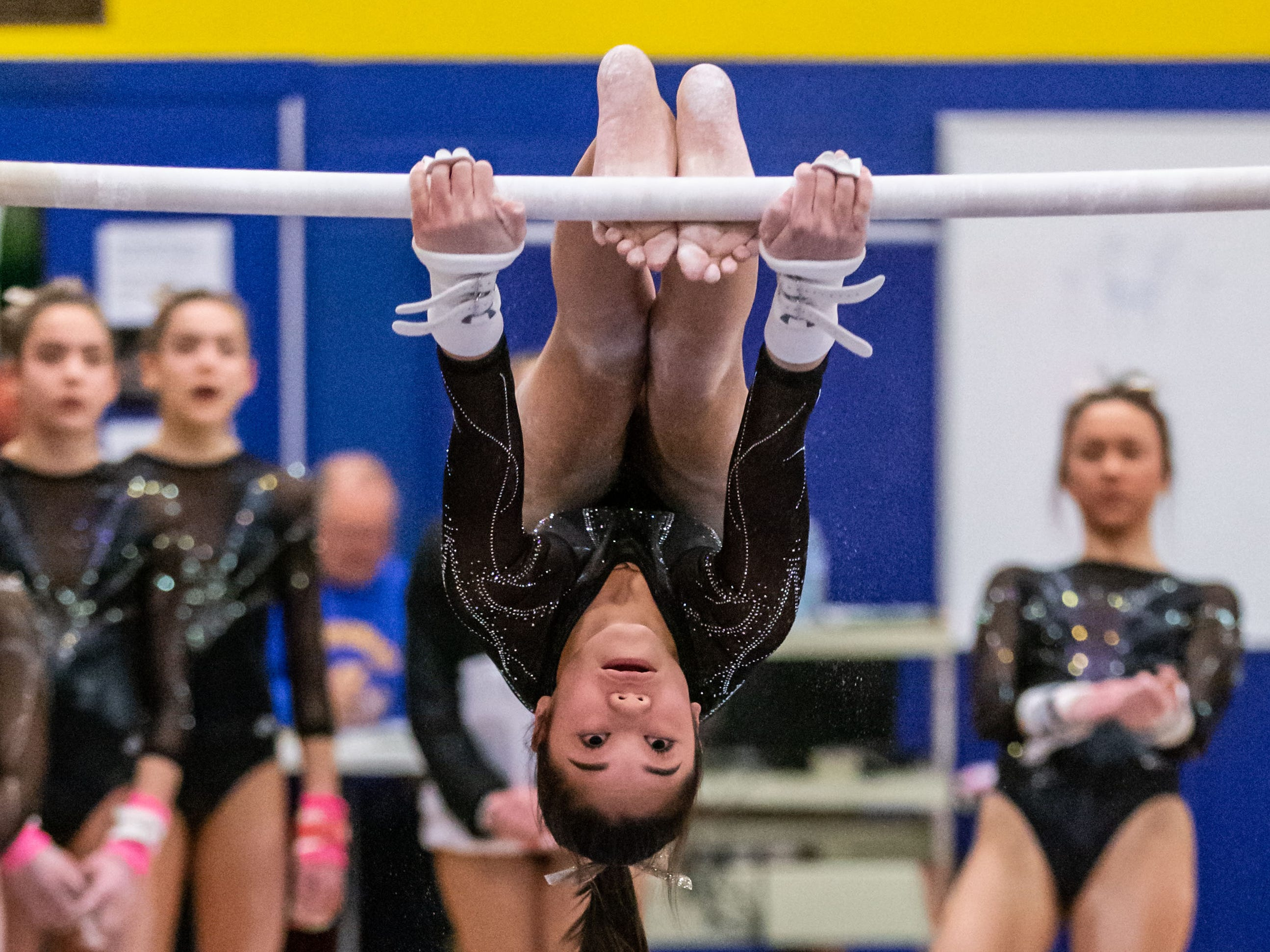 Teammates look on as Franklin/Muskego/Oak Creek/Whitnall co-op gymnast Izzy Wong competes on the bars during the Mukwonago Gymnastics Invite on Thursday, Jan. 10, 2019. Wong placed third on the event with a score of 9.150.