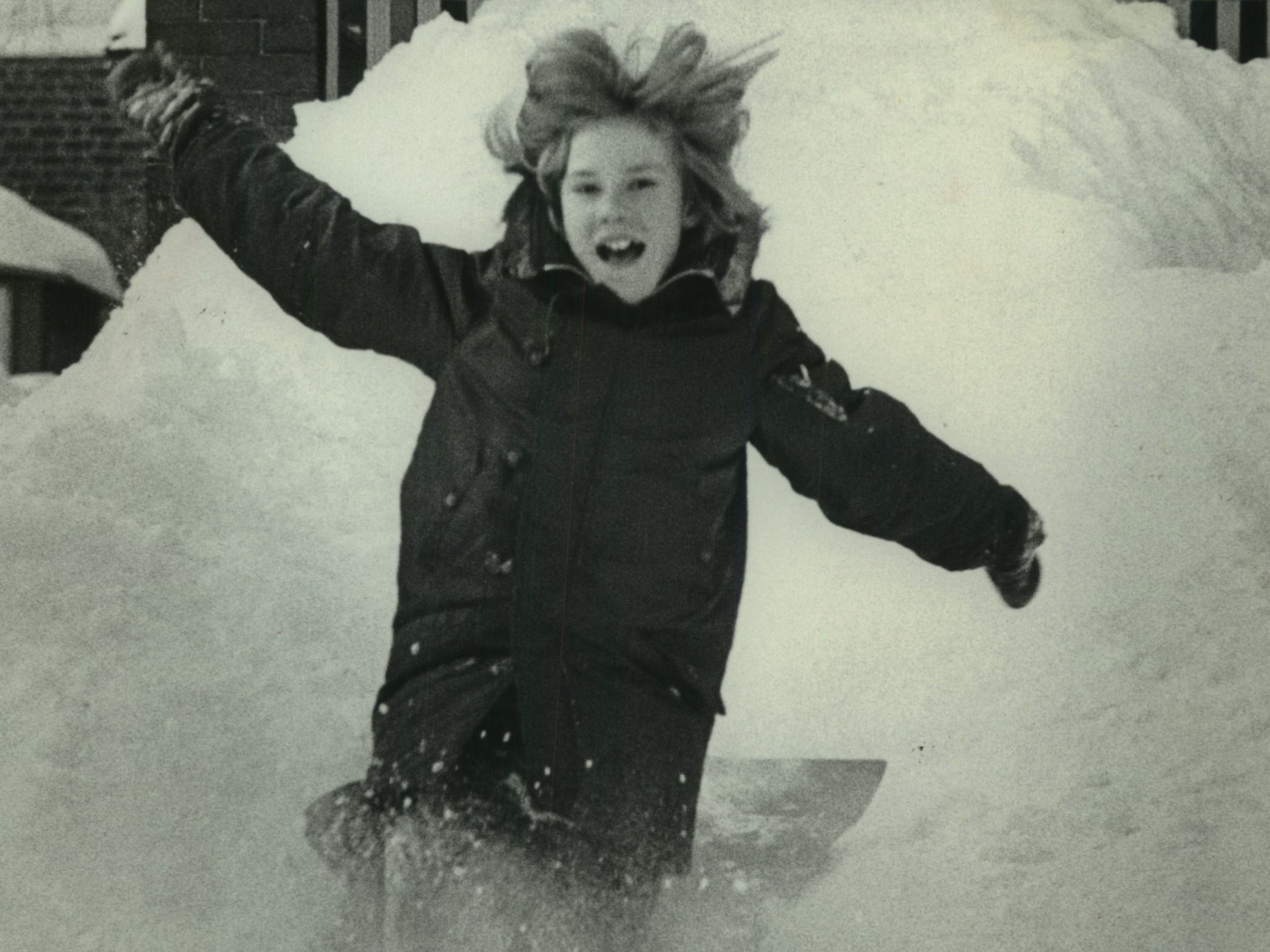 Alecia Litzau slides down a hill of snow that she and her friends made all the way up to her house's porch railing on Milwaukee's east side. This photo was published in the Jan. 17, 1979, Milwaukee Journal.
