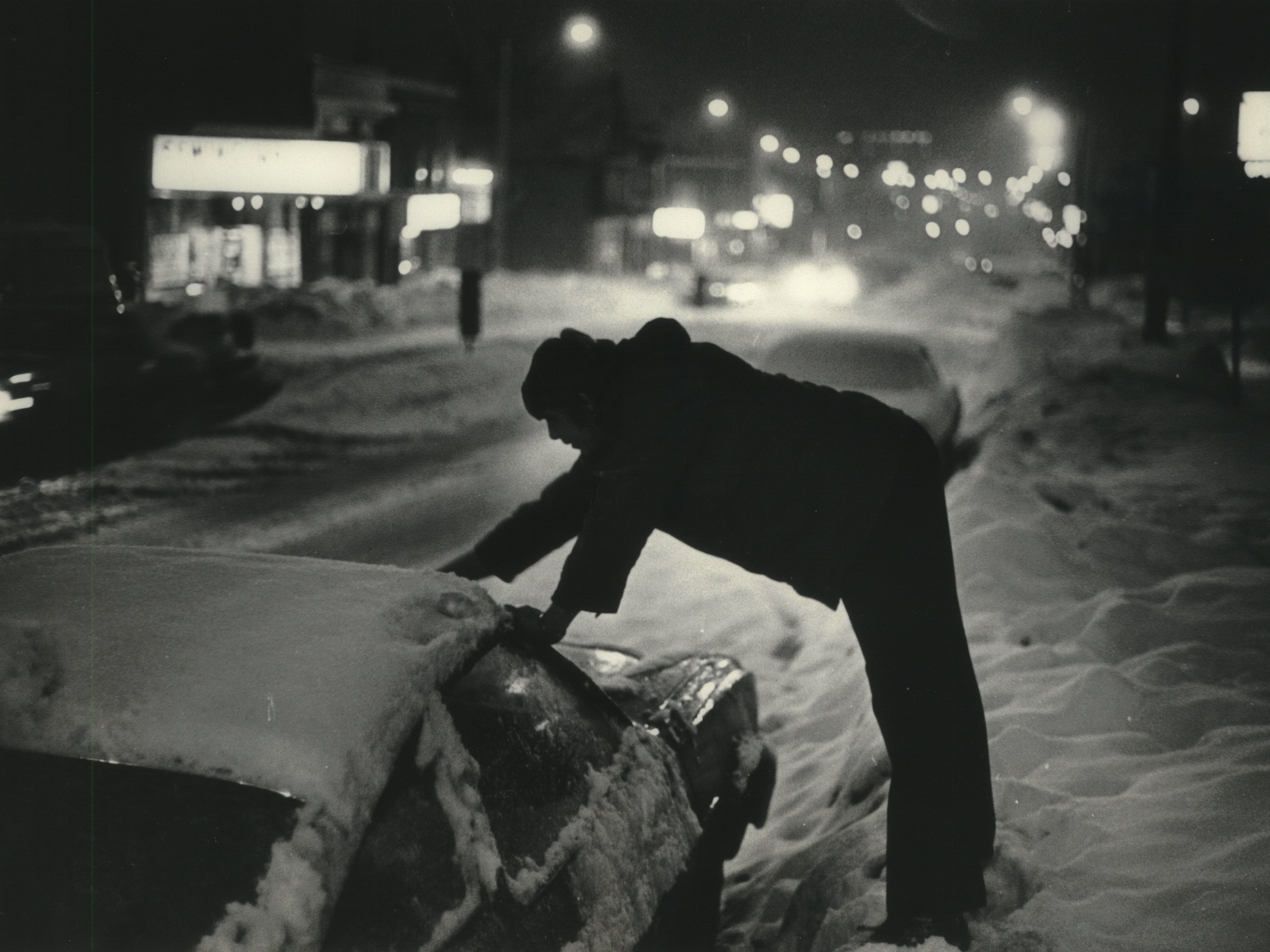Kevin Witkowski stands on a snowbank to reach his windshield to clear it off on West National Avenue on Jan. 23, 1979, during Milwaukee's third major snowstorm in less than a month. This photo was published in the Jan. 24, 1979, Milwaukee Journal.