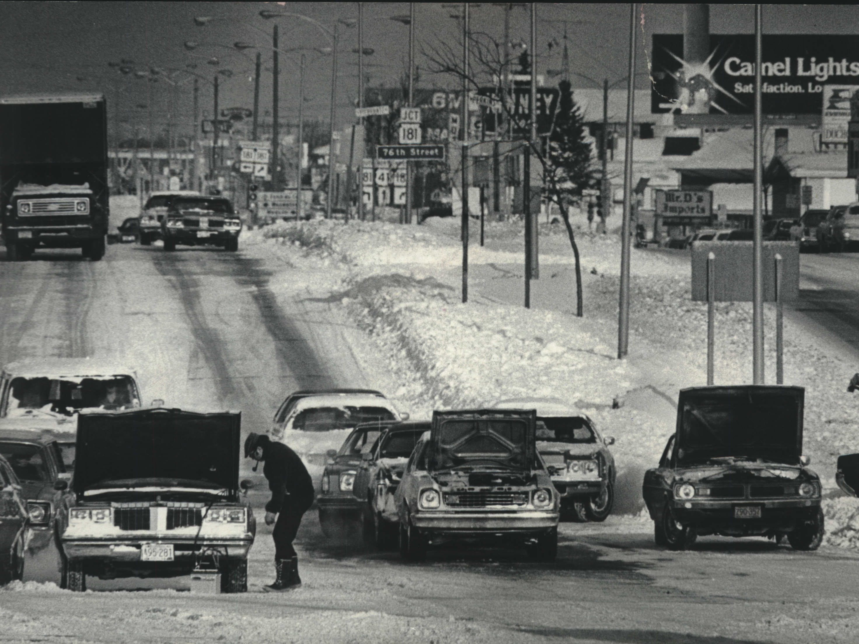 Cars beaten by two days of bitter cold seemingly commiserate on Appleton Avenue near 6th Street on Jan. 2, 1979. Subzero temperatures hit Milwaukee after a New Year's Eve/Day snowstorm that dumped more than 14 inches of snow on the area and closed down Mitchell International Airport. This photo was published in the Jan. 2, 1979, Milwaukee Journal.