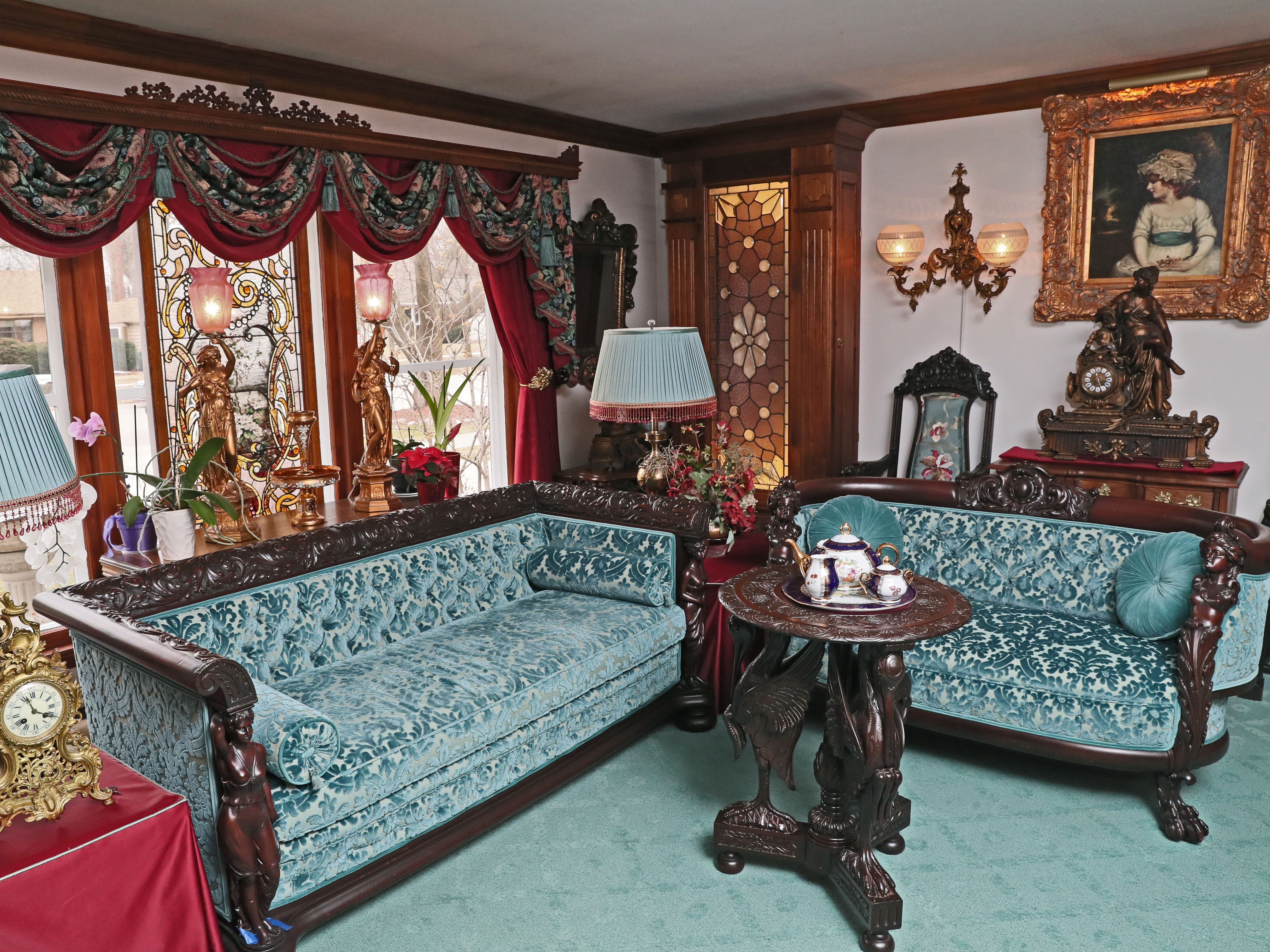 The living room features mahogany furniture reupholstered in teal sculpted velvet.
