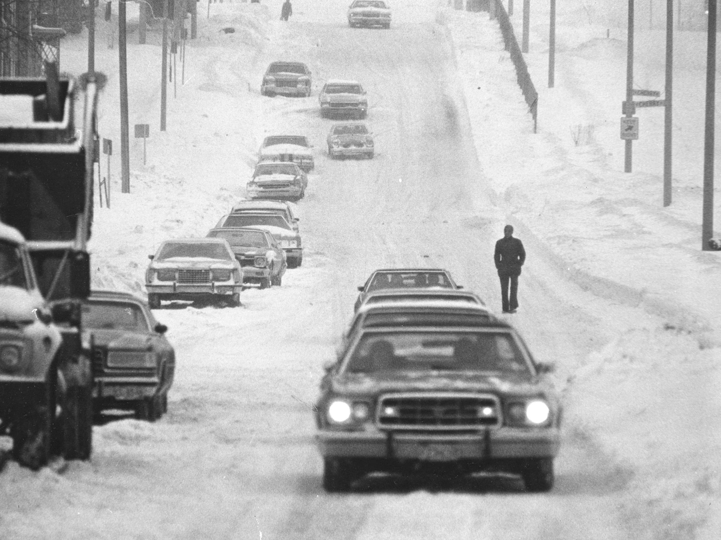 On this stretch of North Sixth Street north of Vliet Street, a pedestrian finds it easier to walk in the street than on the unplowed sidewalks on Jan. 19, 1979. City cleanup crews were running out of places to put the snow. This photo was published in the Jan. 20, 1979, Milwaukee Journal.