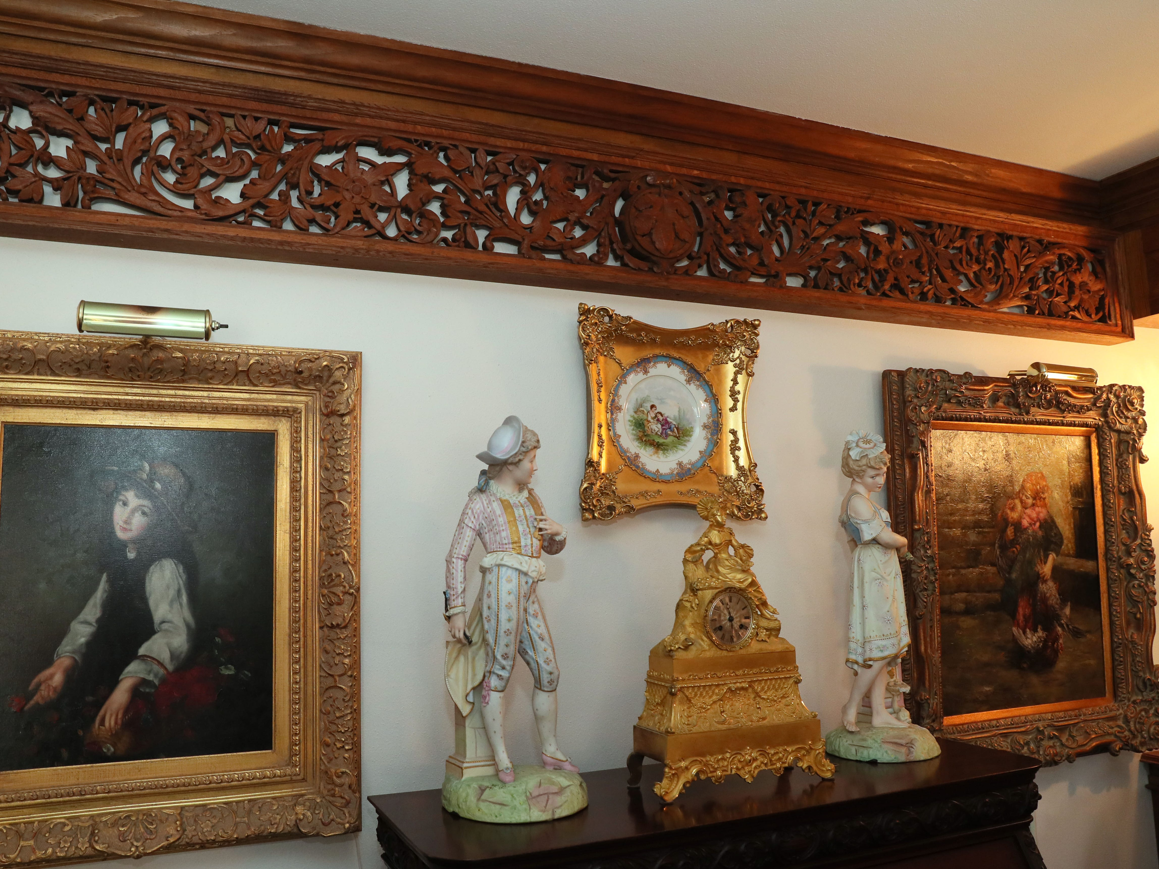 The decorative carving at top is from the Schandein Mansion. The French Monumental clock dates back to the 19th century.