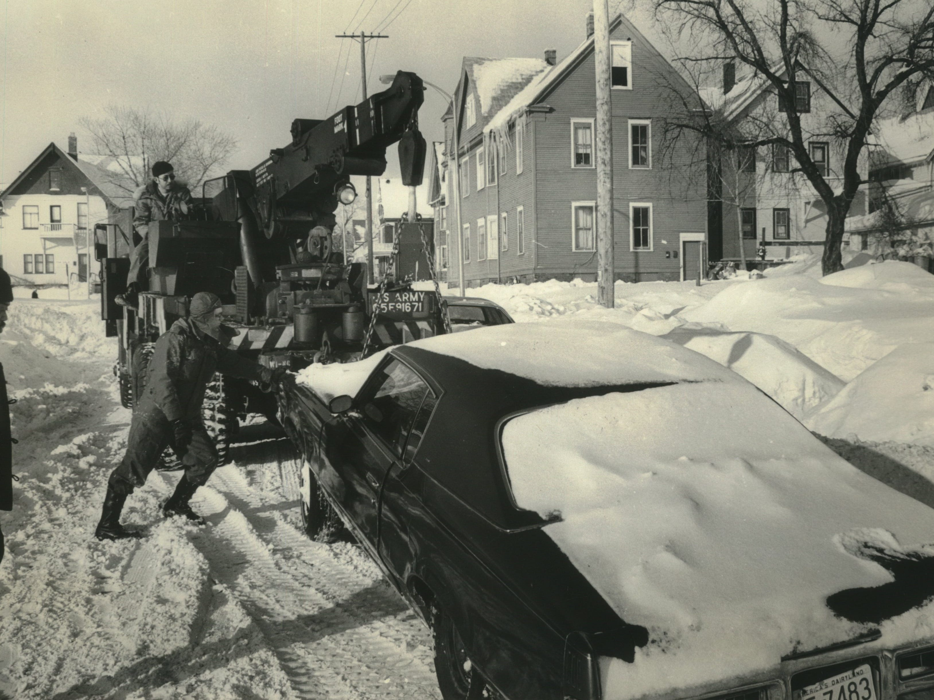 National Guard Sargent Ellston White (foreground) and Master Sargent Jack Harrahan move a car out of the snow at 28th and Walnut streets on Jan. 17, 1979. The National Guard was called out to help city crews clear streets after Milwaukee was socked with its second major snowstorm in two weeks. This photo was published in the Jan. 18, 1979, Milwaukee Journal.