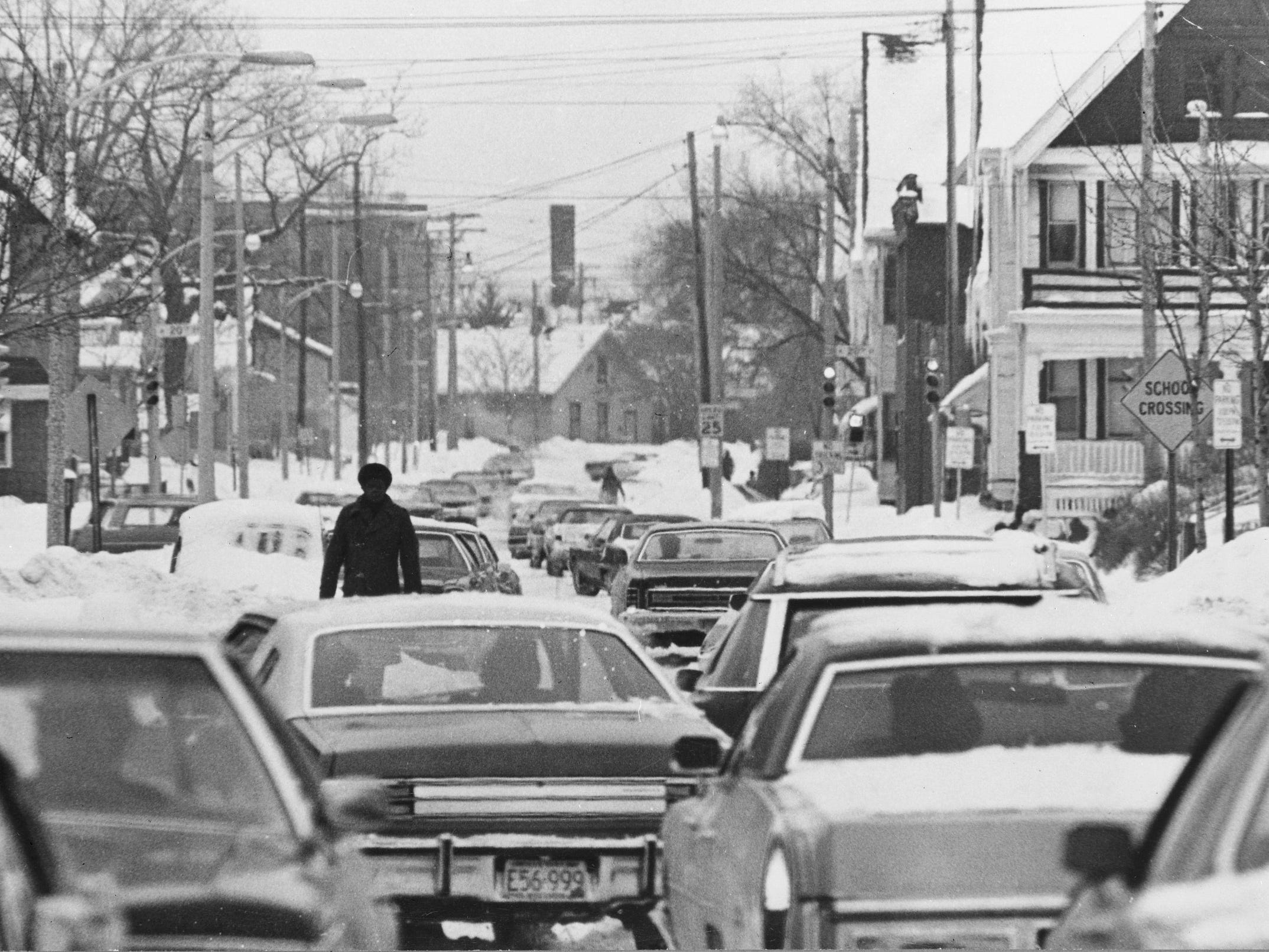 Cars and a single pedestrian try to make their way down West Meinecke Ave. at North 20th Street on Jan. 17, 1979. Milwaukee, still digging out from under its second major snowstorm in two weeks, wrestled with streets narrowed by unplowed snowdrifts and snow-buried cars into March of that year. This photo was published in the Jan. 18, 1979, Milwaukee Sentinel.