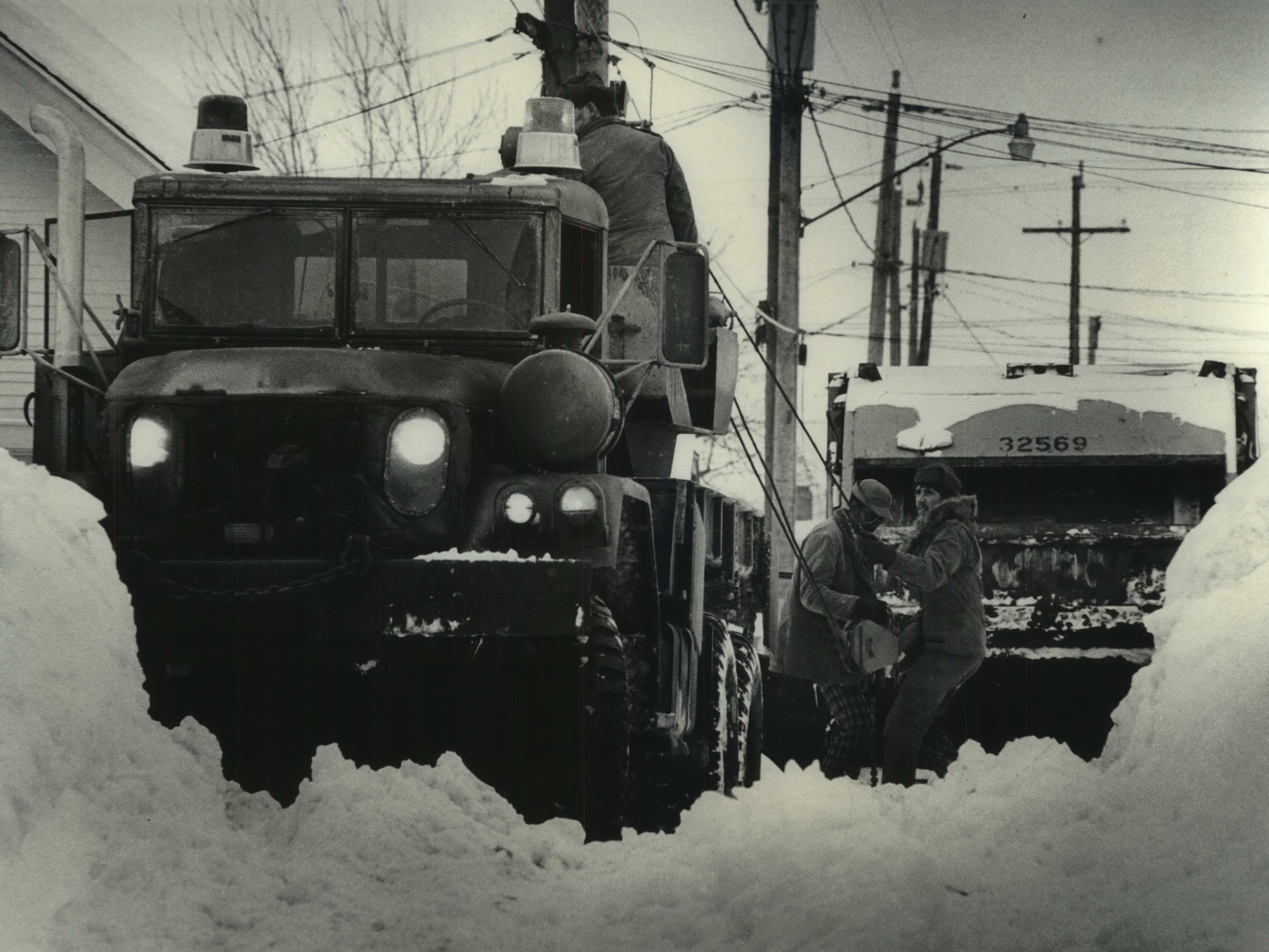 Spec. 5 Timothy Wedekind (right) of Baraboo and a city garbage truck driver test tow cables stretching from one of the National Guard tow trucks sent to Milwaukee to aid in snow emergency operations on Jan. 17. 1979. Staff Sgt. John Brown of Oregon manned the controls on the tow truck. The two guardsmen are attached to Company D, 132nd Support Battalion. The garbage truck was stuck in the snow in an alley between North 53rd and North 54th streets at West Hadley Street. This photo was published on the front page of the Jan. 18, 1979, Milwaukee Sentinel.