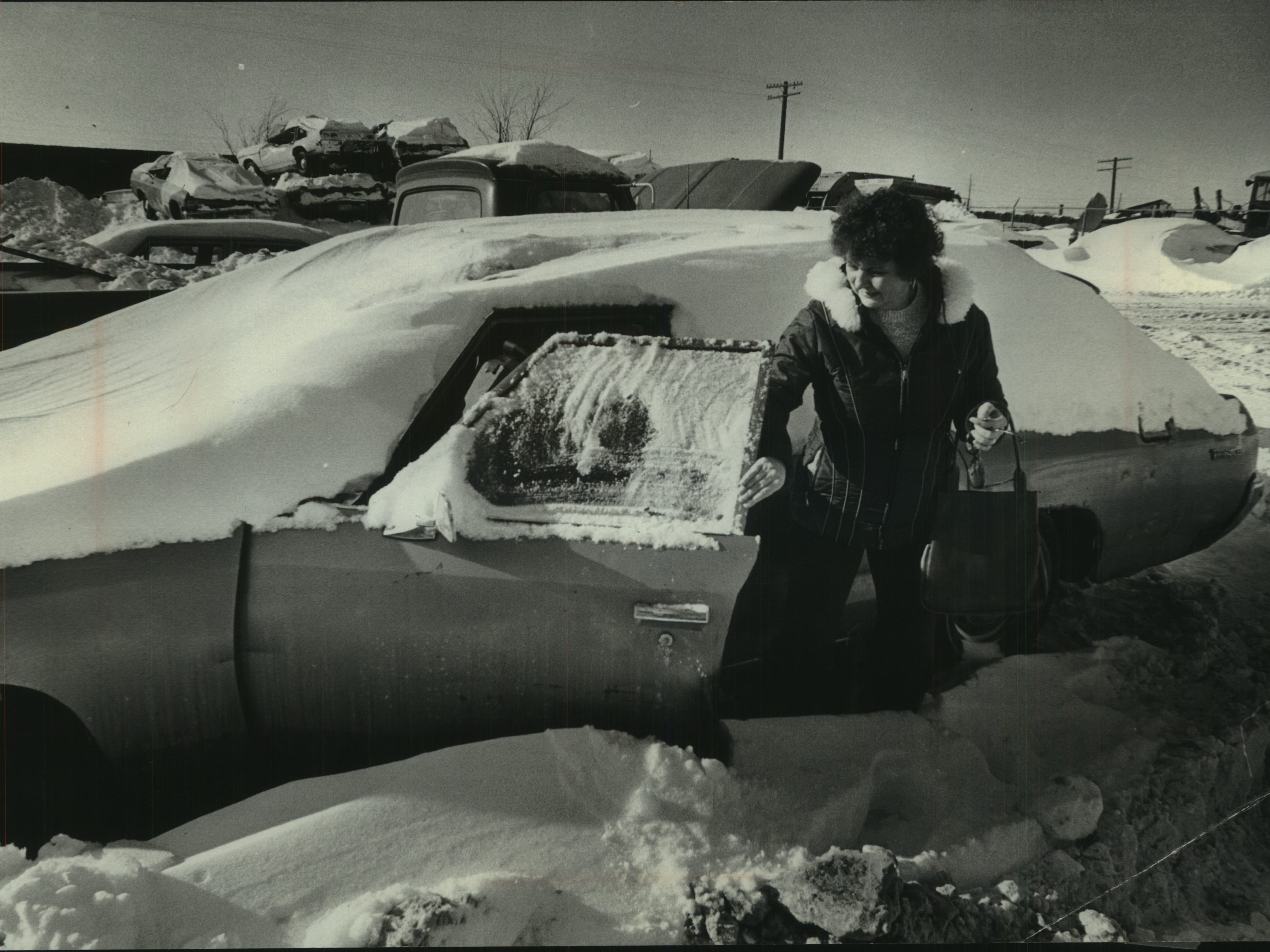 Lucy Krajna checks her car after it was towed to a lot at 30th Street and Ruby Avenue on Jan. 25. 1979. Krajna's car had been towed to the lot after city workers determined it had been abandoned during one of the major snowstorms that hit the city that month; Kracja said the car had been left because a battery cable had burned out in an attempt to drive it in the heavy, wet snow. (She paid the $30 fine, plus $2 a day for when the car was in the lot.) This photo was published in the Jan. 26, 1979, Milwaukee Journal.