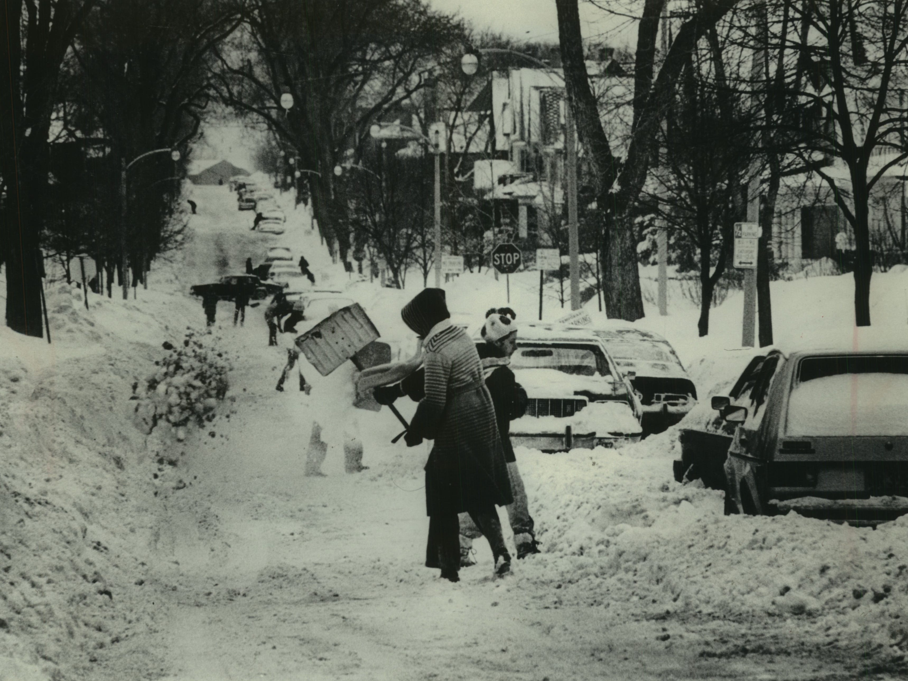 Motorists race to dig cars out of the snow along North Farwell Avenue on Jan. 24, 1979. Police warned that cars parked on the street would be towed to clear the way for plowing operations; by then, the city had towed hundreds of abandoned cars to storage lots. This photo was published in the Jan. 25, 1979, Milwaukee Sentinel.