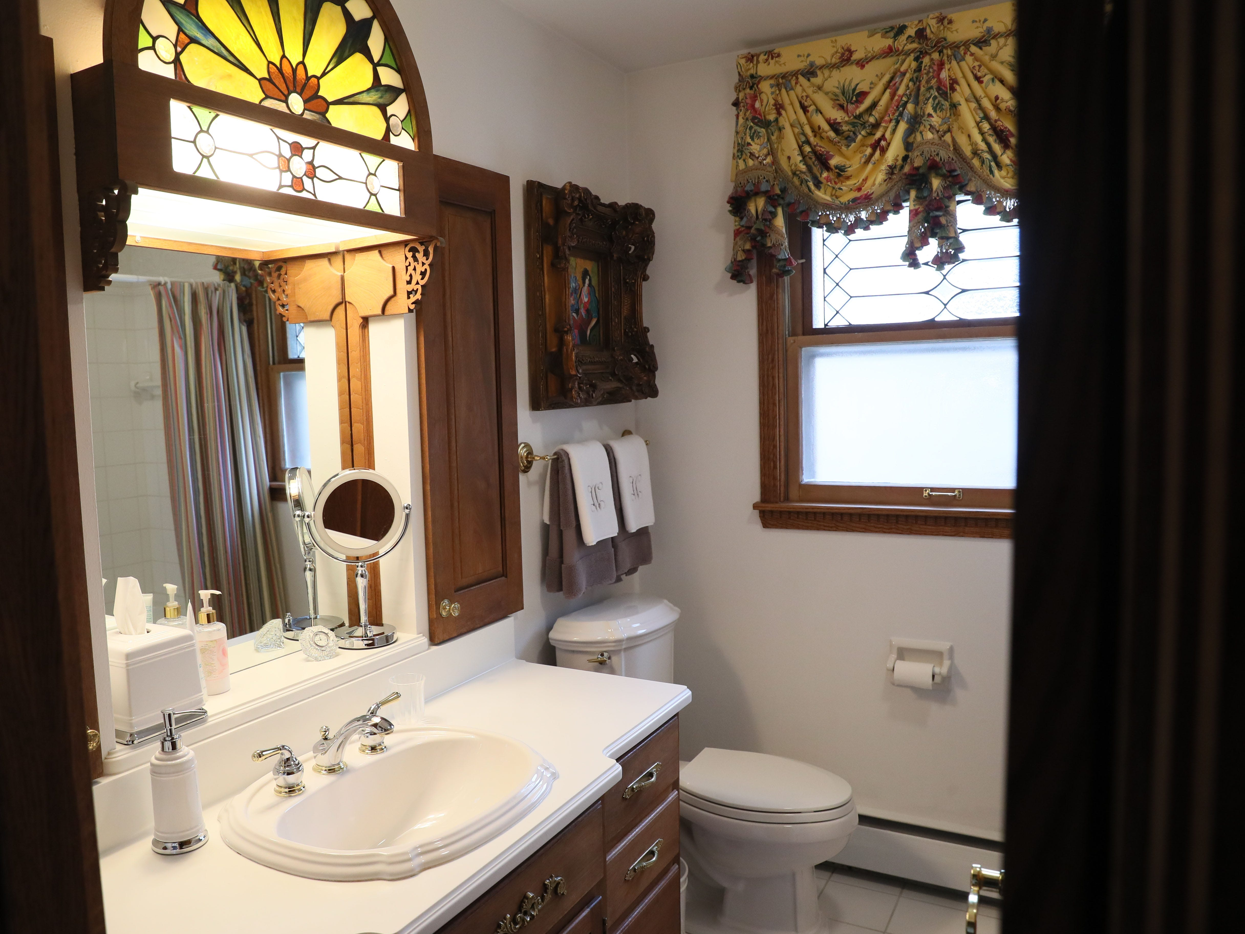 The bathroom features a stained glass light and formal window treatment.