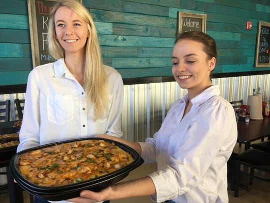 Servers Melissa Chance, left, and Lisa Dennis hold a platter of shrimp and grits at the grand opening of Mahi Mike's in Prattville.