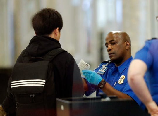 A Transportation Security Administration employee checks an air traveler's identification at Hartsfield Jackson Atlanta International Airport Monday, Jan. 7, 2019, in Atlanta. (AP Photo/John Bazemore)