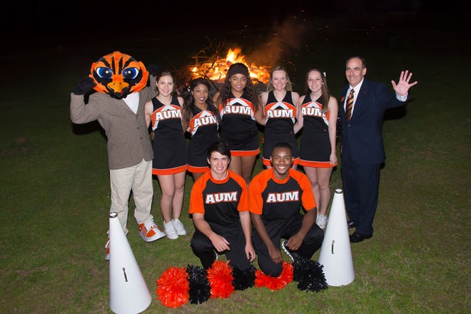 Chancellor Carl A. Stockton, Curtiss the Warhawk and the AUM cheerleading squad enjoy a pep rally bonfire during a previous AUM Homecoming.