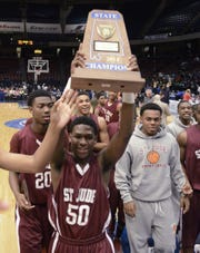 St. Jude's Keondre Davis raises the Class 1A boys basketball championship trophy in February 2014. It ended up being the Pirates' final game.