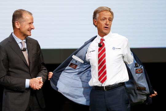 Dr. Herbert Diess, CEO, Volkswagen AG, left, watches Tennessee Gov. Bill Haslam show his shirt during media previews for the North American International Auto Show in Detroit, Monday, Jan. 14, 2019.