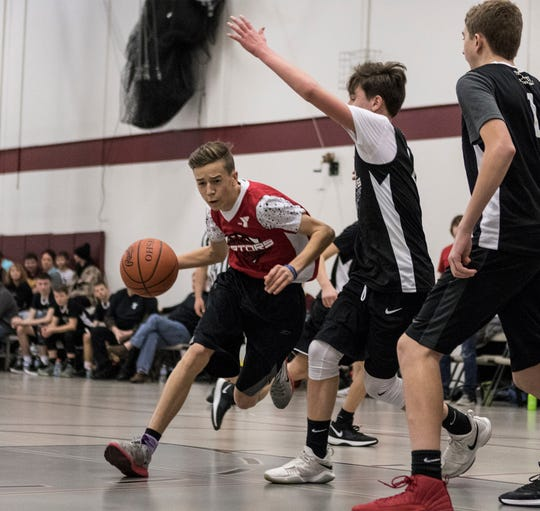 Logan Cook, 15, of Pataskala playing on the Raptors dribbles the ball past the Warriors during a youth basketball game at the Licking County YMCA Sunday.