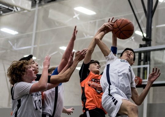 Dominick Costa of Granville grabs the rebound from Grant Edwards of Columbus Academy during a youth basketball game at the Licking County YMCA Sunday.