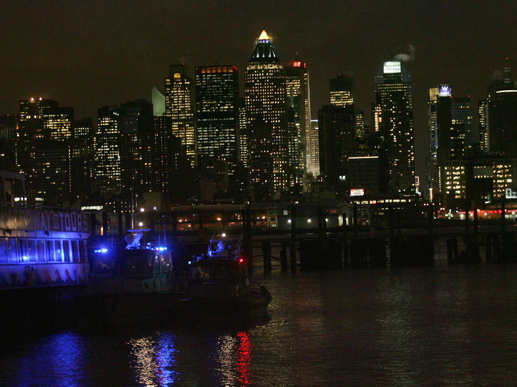 Boats flashing red and blue lights are shown docked at Port Imperial in Weehawken, across from midtown.