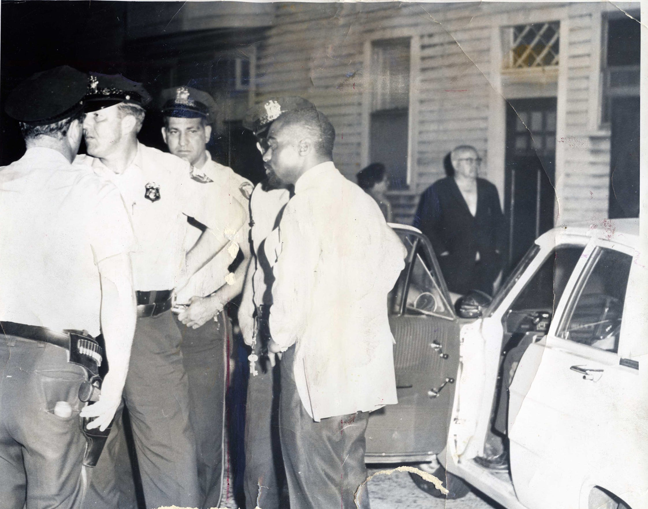 "Rubin ""Hurricane"" Carter, right, chats with police at the scene of a triple murder in June 1967. The boxer and his sparring partner John Atis were arrested and charged with three counts of homicide at the Lafayette Grill in Paterson."