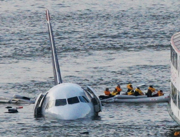 In this Jan. 15, 2009 file photo, passengers in an inflatable raft move away from an Airbus 320 US Airways aircraft that has gone down in the Hudson River in New York.