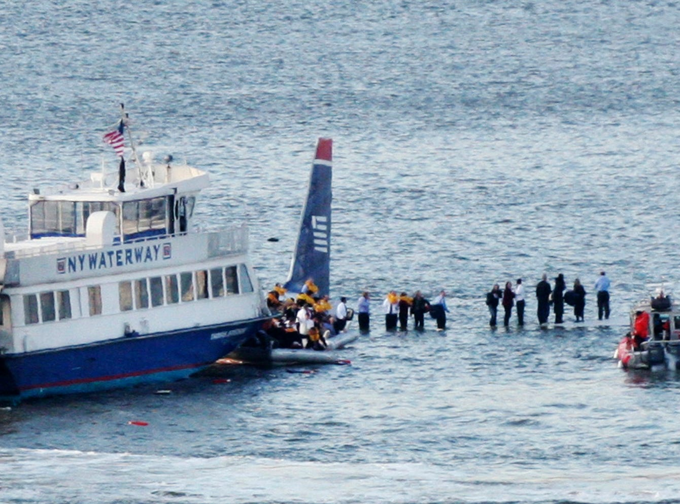 "In this Jan. 15, 2009, file photo, ferry boats surround a US Airways aircraft that went down in the Hudson River in New York as passengers stand on the wings of a US Airways jetliner on the Hudson River. Pilot Chesley ""Sully"" Sullenberger and air traffic controller Pat Harten are forever linked because of the amazing outcome for all 155 passengers."