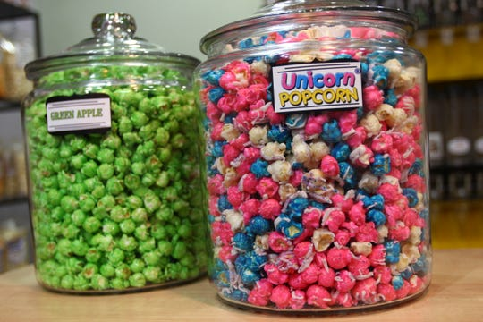Unicorn and green apple popcorn look colorful in their jars at International Popcorn.