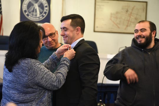 New Teaneck Police Officer Nicholas Ruscigno receives his badge from his mother, Theresa, while his father, Frank, and brother James watch. Ruscigno was sworn in on Monday, January 14, 2019, in the Teaneck council chambers.