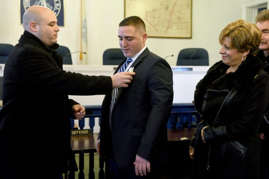 Teaneck Police Officer Philip Apreda pins on the badge of his cousin, Michael Apreda, with Michael's mother, Theresa Apreda, watching on Monday, January 14, 2019, in the Teaneck council chambers.