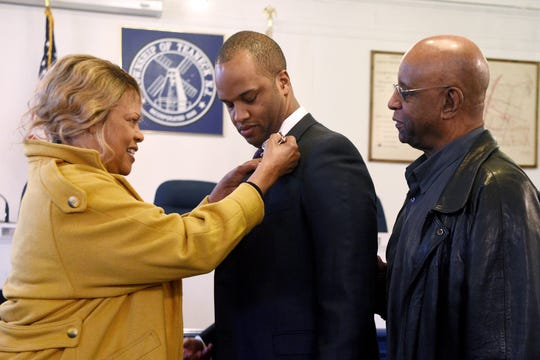 New Teaneck Police Officer Brandon Graham receives his badge from his mother, Janet Graham, as his father, John Graham, watches. Graham was sworn in on Monday, January 14, 2019, in the Teaneck council chambers.