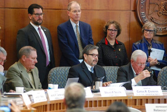 New Mexico lawmakers including Sen. Carlos Cisneros, left, D-Questa, and House Speaker Brian Egolf, upper left, D-Santa Fe, announce a proposal on Monday, Jan. 14, 2019, in Santa Fe N.M. for an 11 percent increase in general fund spending for the coming fiscal year amid a surge in state government income. Most of the new spending would go toward efforts to improve public education as the judiciary threatens to intervene to ensure adequate resources for struggling schools.