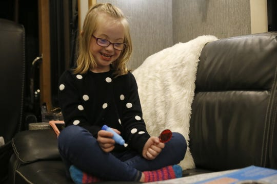 Grace Leaverton plays on a couch, Friday in her family's RV while parked at the Bluffview RV Park in Farmington.