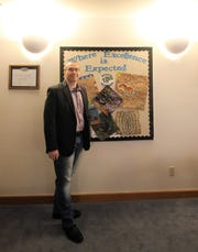 "Ruidoso Municipal School District Superintendent Dr. George Bickert stands proudly at the district office in front of what it ""means to be a dedicated"" member of the school system. Bickert takes pride in the staff and students in the district."
