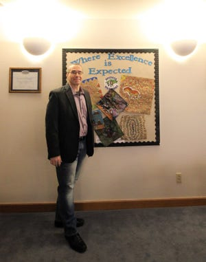 """Ruidoso Municipal School District Superintendent Dr. George Bickert stands proudly at the district office in front of what it """"means to be a dedicated"""" member of the school system. Bickert takes pride in the staff and students in the district."""
