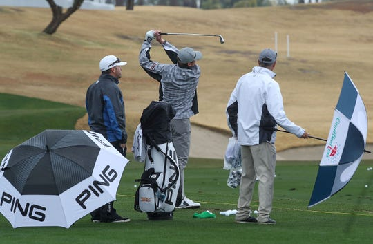 Golfers get in some practice during slowdowns in the rain at the Desert Classic at PGA West in La Quinta, January 14, 2019.