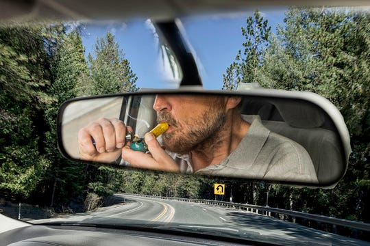 Stock photo of a man smoking cannabis in a moving vehicle .