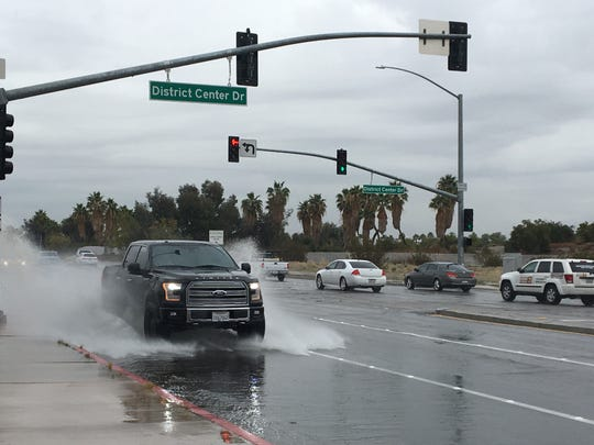A pickup drives through rainwater on Gene Autry Trail. The area was hit by a storm that's expected to drop an inch of rain this week.