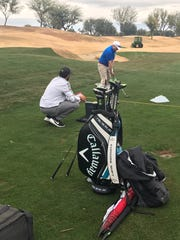 Navy veteran Shane McKenzieo prepares to hit a shot under the watchful eyes of a Callaway club fitting expert at PGA West Monday.