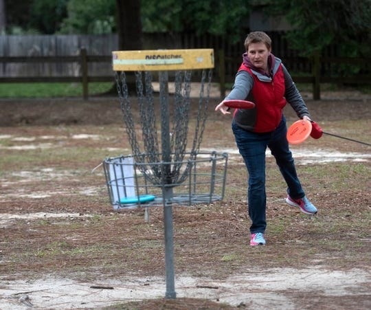 Tami Brown tries her luck at the disc golf course Monday at Hitzman-Optimist Park on Langley Avenue.