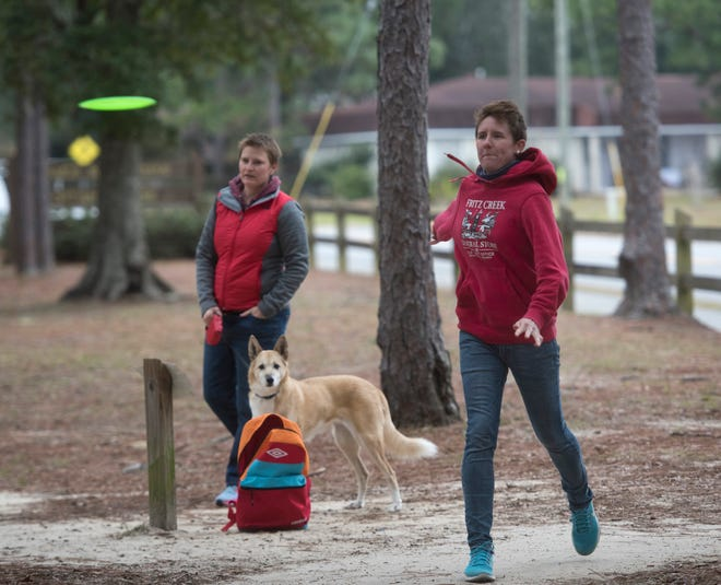 Amie Grenoble plays disc golf on Monday at Hitzman-Optimist Park in Pensacola as Tami Brown and her dog, Pumpkin, look on.