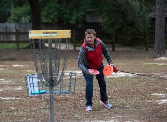 Tami Brown tries her luck at the disc golf course at the James Hitzman Optimist Park on Langley Ave. on Monday, Jan. 14, 2019. The city of Pensacola is working on a plan to swap the YMCA property on Langley to build dedicated soccer fields at the Northeast Pensacola park.