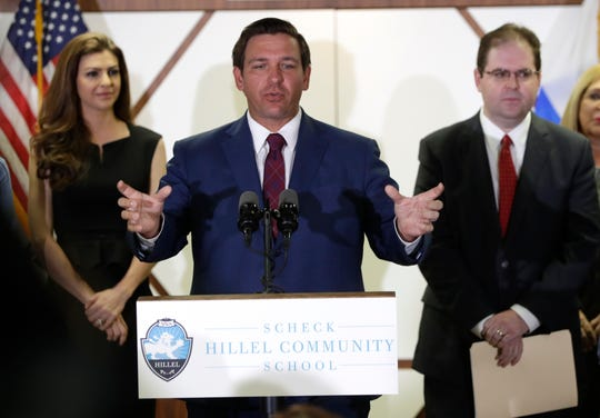 Republican Gov. Ron DeSantis, center, speaks after announcing the appointment of former federal prosecutor and Miami appeals court judge Robert Luck, right, to a seat on the Florida Supreme Court, Monday, Jan. 14, 2019, in Miami. (AP Photo/Lynne Sladky)