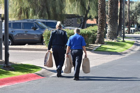 TSA employees walking away with food distributed during a mobile food pantry hosted by St. Mary's Food Bank at the TSA offices at Gateway Tower