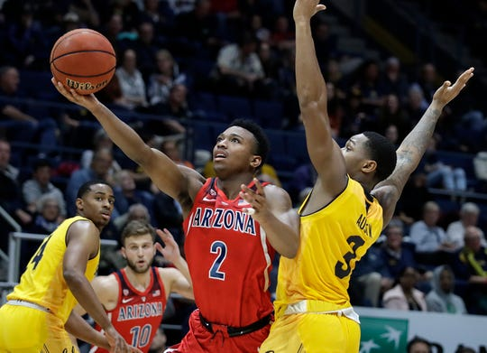 Arizona's Brandon Williams (2) lays up a shot past California's Paris Austin, right, in the second half of an NCAA college basketball game Saturday, Jan. 12, 2019, in Berkeley, Calif.