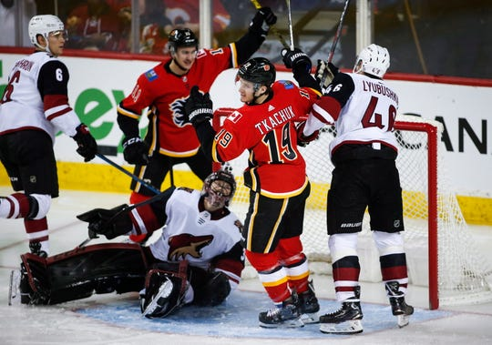 Arizona Coyotes goalie Adin Hill looks on as Calgary Flames' Matthew Tkachuk (19) celebrates his goal during the second period of an NHL hockey game, Sunday, Jan. 13, 2019, in Calgary, Alberta.