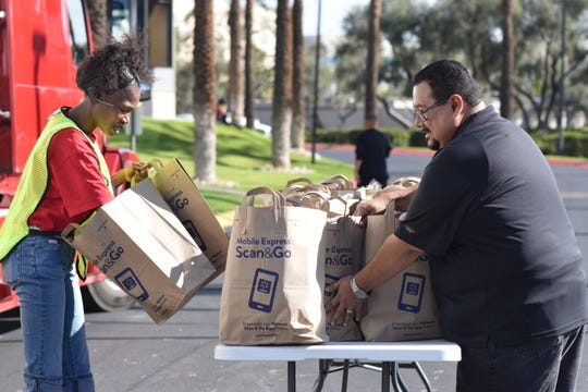 Volunteers hand out food to TSA employees during a mobile food pantry event at TSA offices in Phoenix hosted by St. Mary's Food Bank