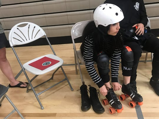 Victoria Peralta, 18, puts on her skates to start practicing at the Arizona Roller Girls meet and greet on Sunday, Jan. 13, 2019.