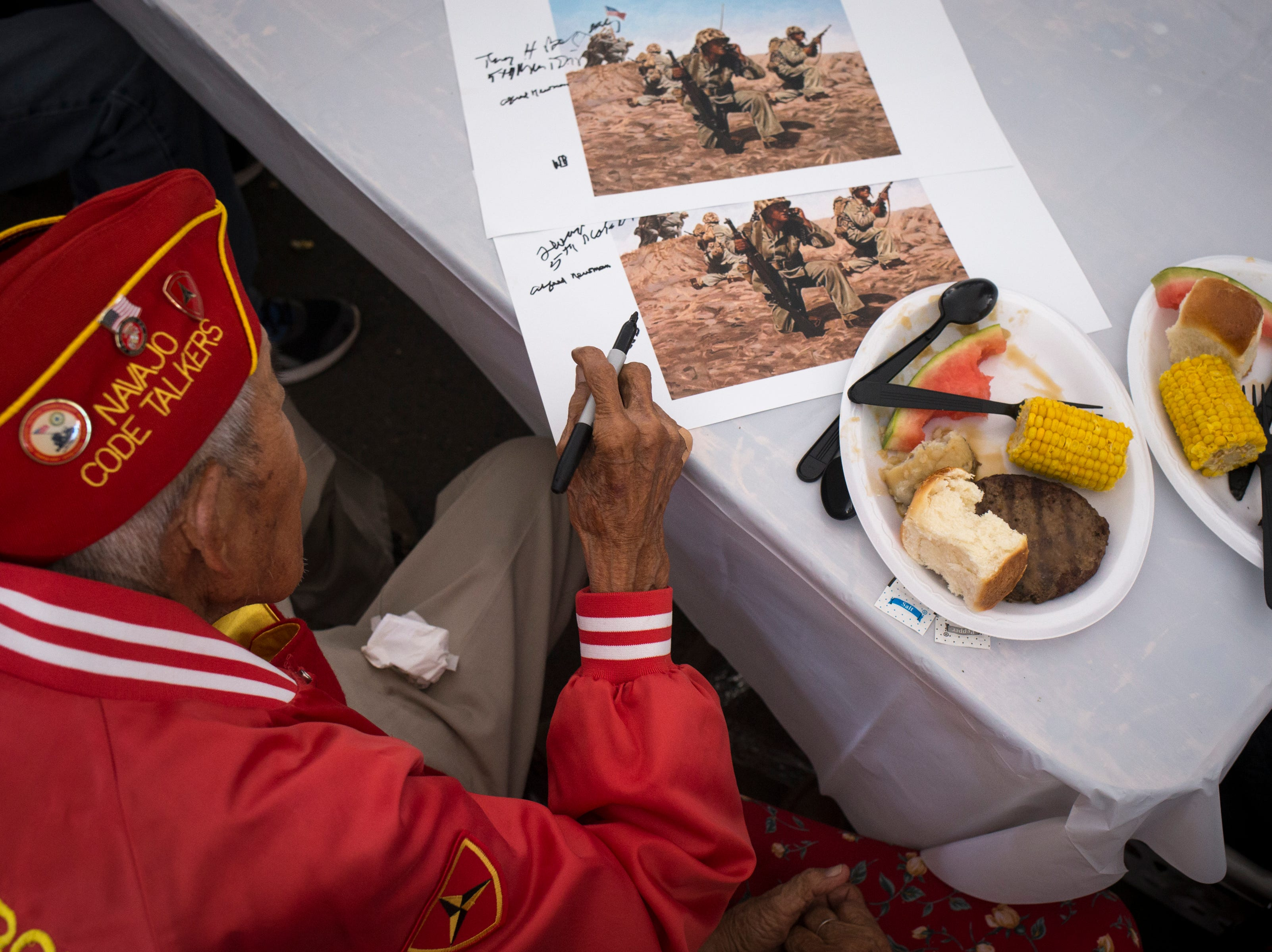Navajo Code Talker Alfred Newman signs a poster after the Navajo Nation Code Talkers Day ceremony Aug. 14, 2018, at the Veterans Memorial Park in Window Rock.